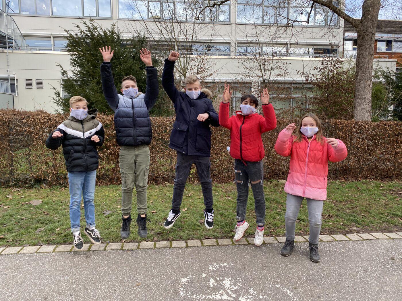 fünf springende Schüler/innen