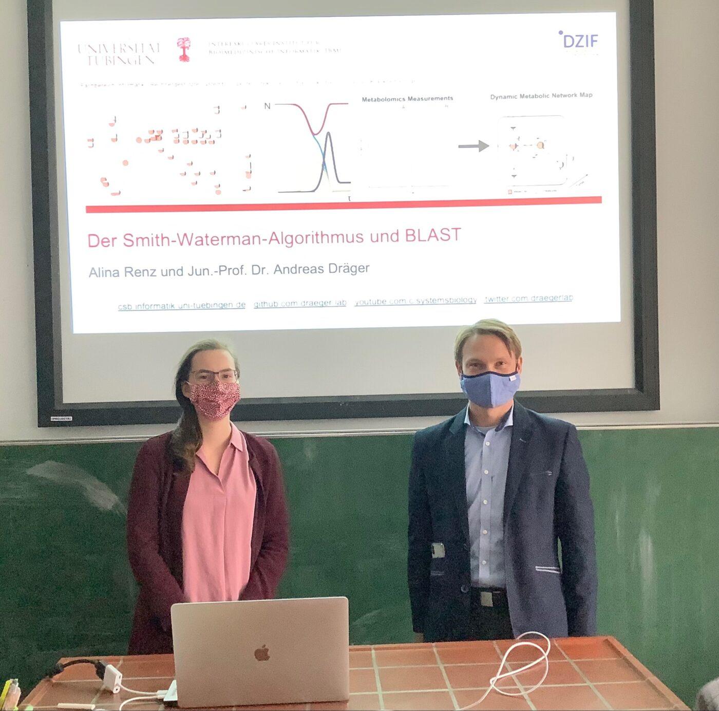 Alina Renz und Jun.-Prof. Dr. Andreas Dräger vor einer PowerPoint Präsentation
